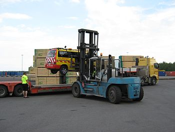 English: Forklift lifting a van onto a truck, ...