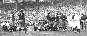 Tackle on the field, in front of a packed grandstand