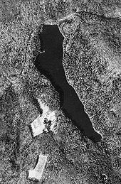 Black and white aerial view of a narrow lake in wooded hills