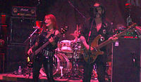 Female musician Enid Williams from the band Girlschool and Lemmy Kilmeister from Motörhead are shown onstage. Both are singing and playing bass guitar. A drumkit is seen behind them.