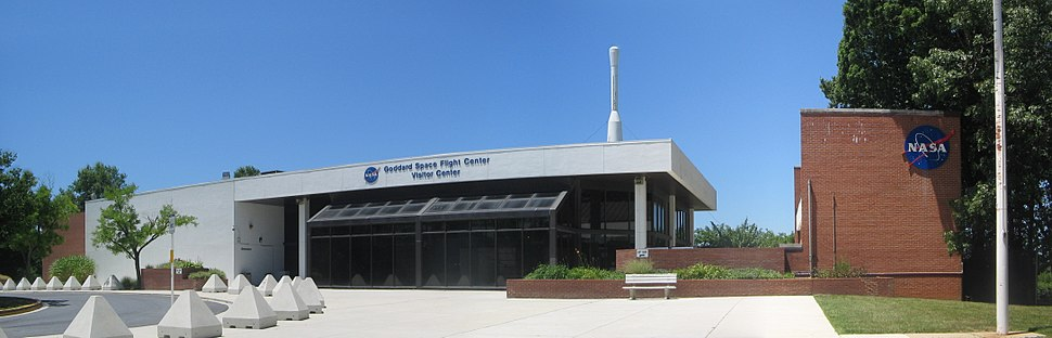 Panoramic view of the Visitor's Center at Goddard Space Flight Center, with the top of a Delta rocket visible behind the main building and the gift shop at right.
