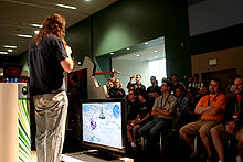 A man wearing a black shirt and jeans and carrying a microphone speaks to a sitting crowd. In the center of the frame is a flatscreen television displaying Halo Wars gameplay.