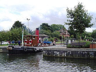 Hambleden Lock - An old tug boat leaves the lock