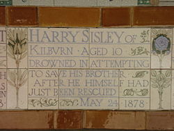 "A tablet formed of five tiles of varying sizes, bordered by yellow and blue flowers in an art nouveau style. The tablet reads ""Harry Sisley of Kilburn aged 10 drowned in attempting to save his brother after he himself had just been rescued May 24, 1878""."