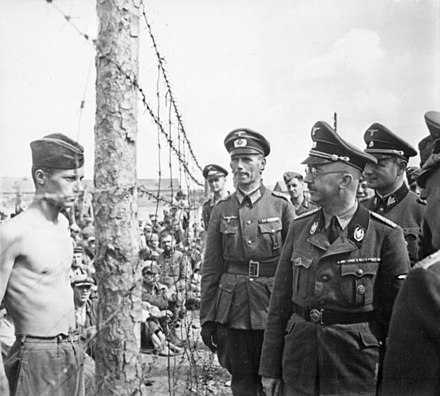Reichsfuhrer-SS Heinrich Himmler, accompanied by an entourage of SS and Heer personnel, inspects a prison-camp for Soviet prisoners-of-war in the fall of 1941. Himmler besichtigt die Gefangenenlager in Russland. Heinrich Himmler inspects a prisoner of war camp in Russia, circa... - NARA - 540164.jpg