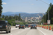 A freeway with traffic cones carrying traffic downhill into a large city