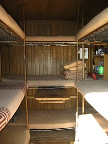 interior of a mountain bivouac hut showing bunk beds