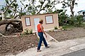 Julia Nazario Fuentes, Mayor of Loiza walking past damaged house in Loíza, Puerto Rico.jpg