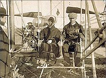 Wilbur and Katharine Wright seated in the Wright Model A Flyer with Orville Wright standing nearby. This was Katharine's first time flying. Her skirt is tied with a string.