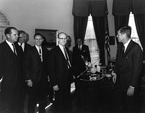 NASA - William H. Pickering, (center) JPL Director, President John F. Kennedy, (right). NASA Administrator James E. Webb (background) discussing the Mariner program, with a model presented.