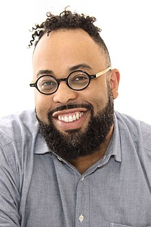 Headshot of Kevin Young. Young, with short hair and a beard, smiles at the camera; he wears a blue shirt and round glasses.