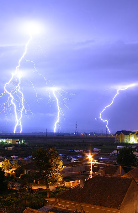 Lightning is an example of plasma present at Earth's surface. Typically, lightning discharges 30,000 amperes at up to 100 million volts, and emits light, radio waves, and X-rays. Plasma temperatures in lightning might approach 30,000 Kelvin (29,727 degC) (53,540 degF), or five times hotter than the temperature at the sun surface, and electron densities may exceed 10 m . Lightning over Oradea Romania 3.jpg