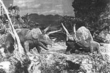 A black-and-white screenshot of three triceratops atop a cliff with trees surrounding them and mountains in the background.