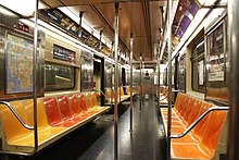 The interior of an R62A car on the 1 train. Its seats are yellow, red, and orange, and it has several advertisements hanging above.