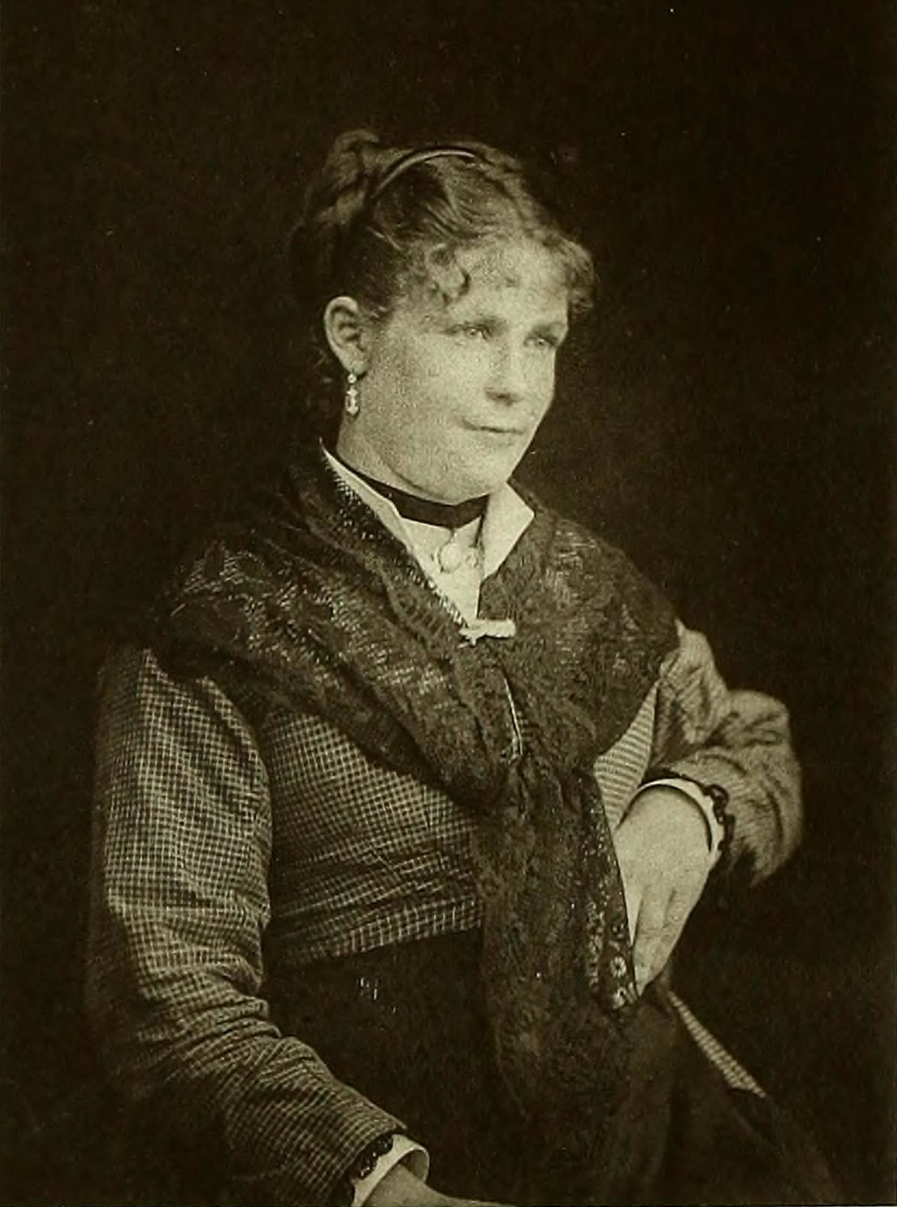 A black-and-white portrait of a young woman wearing a checkered dress and a shawl