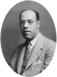 Photograph showing the head and shoulders of a man with glasses wearing a suit