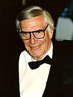 A picture of a man in his late sixties. He is wearing a tuxedo and a black bowtie.