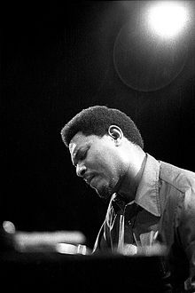 Close-up, worms eye-view of McCoy Tyner at a piano, backlit