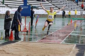 Athlète handisport atterrissant au saut en longueur, de face, les bras en l'air.