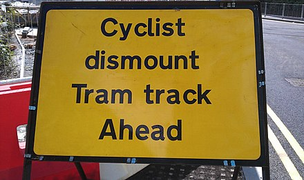 A sign advising cyclists to dismount due to tram tracks. Tram tracks pose a hazard for cyclists, as their wheels may get caught in the track. Midland Metro - Cyclist dismount sign - Andy Mabbett.jpg