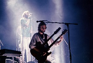 Multi-neck guitar - Mike Rutherford of Genesis, circa 1980, playing a double-necked guitar with a Shergold twelve-string/bass configuration