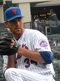 A man in a white pinstriped baseall uniform and blue cap winds up to throw a baseball.