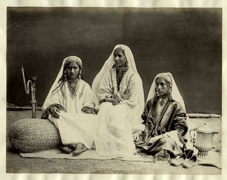 A photograph of three young nautch girls sitting together, taken in Kashmir