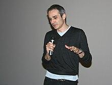 Homme de 53 ans, mince, portant un pull gris sur un T-shirt clair près du corps, courts cheveux gris, qui parle dans un micro
