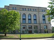 Un edificio municipal de color beige de cinco pisos con grandes ventanas arqueadas.  Un árbol está enfrente del edificio.