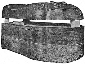 Black and white image of a dark stone coffin viewed laterally, the coffin lies on the ground, the trough and lid are separated with wedges.