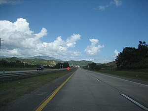 Puerto Rico Highway 53 - A typical stretch of the PR-53 freeway through Humacao, Puerto Rico with the El Yunque peak in the distance.