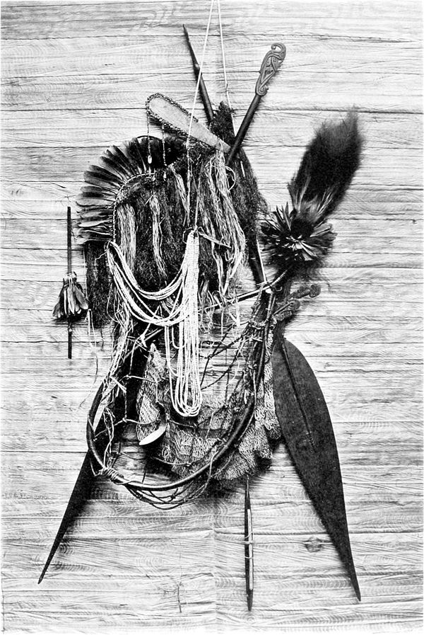 Black and white photograph of a collection of native implements, including paddles and ornaments.
