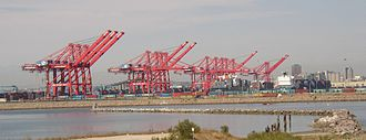 Container port - Pier T Container Terminal in Long Beach, California, U.S. with intermodal rail in the foreground and gantry cranes behind that