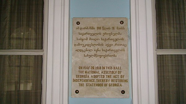"Bilingual plaque: ""On May 26, 1918, in this hall the National Council of Georgia adopted the act of independence, thereby restoring the statehood of Georgia"". Plaque commemorating the 1918 establishment of the First Georgian Republic.jpg"