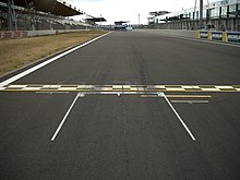 starting box on racetrack, with checkered starting and finishing line in front