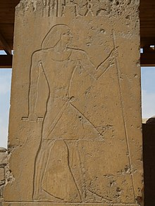 Relief of a man standing holding a staff