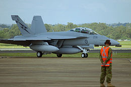 Twin-finned military jet on an airfield, with a ground crewman in an orange vest in the foreground