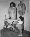 "REA, ""Woman irons daughter's dress, girl holding doll"" - NARA - 195872.tif"