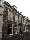 Huis met witgeschilderde lijstgevel waarin horizontale natuursteenbanden te onderscheiden zijn