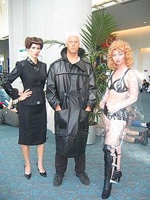 Trois personnes habillées et coiffées se tiennent debout.