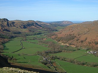 River Esk, Cumbria - View of Eskdale: the tree-lined Esk enters bottom right, passing Brotherilkeld Farm and continuing down the valley to the Irish Sea which can be seen in the far distance
