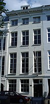 foto van Koopmanshuis, met gebosseerde, natuurstenen gevel en kroonlijst. Schuiframen en balconhekjes, 19e eeuw