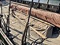 Saga Oseberg Details wood deck (skipsdekk) canvas tarp wrapped in yard (rå bom) ores (årer) oreholes (årehull) shroud pins (vant) etc. Viking ship replica 2012 Tønsberg harbour Norway 2019-08-24 IMG 0245.jpg