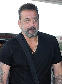 Dutt posing for the camera in a black T-shirt, also carrying a strap bag