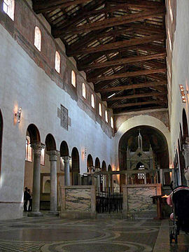 The interior of a narrow and rather dark church that has columns down each side supporting a plain wall with small high windows.