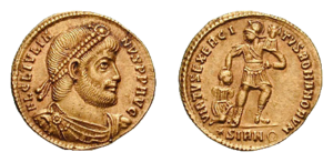 "Roman army - Coin showing (obverse) head of the late Roman emperor Julian (ruled 361–363 AD) wearing diadem and (reverse) soldier bearing standard holding kneeling barbarian captive by the hair, legend and Myth VIRTUS EXERCITUS ROMANORUM (""Valour of the Roman army""). Gold solidus. Sirmium mint."