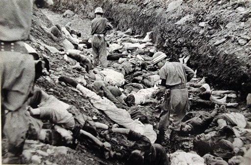 South Korean soldiers walk among dead political prisoners, Taejon, South Korea