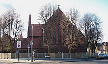A red brick church, with very tall thin windows and no spire or tower