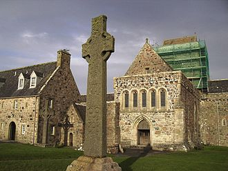 History of Christianity in Scotland - The 9th century St Martin's Cross, with St John's cross in the background, stands outside the entrance to Iona Abbey