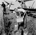 StateLibQld 1 117540 Pouring oil to refuel a biplane, Blackall, 1941.jpg
